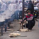 Мужчина топит казаны во время приготовления полторы тонны бешбармака в Бишкеке