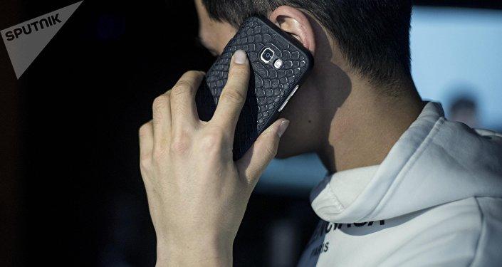 Телефон кармаган жигит. Архивдик сүрөт
