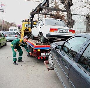 Сотрудники эвакуируют автомобиль за неправильную парковку в Оше