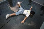 Мальчик ложится, чтобы увидеть вид сквозь стекло на стеклянном мосту в Китае. Архивное фото