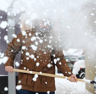 Мужчина с лопатой во время уборки снега. Архивное фото