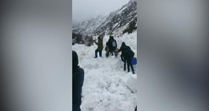 Очевидец снял на видео, как люди поднимаются на 50-метровую гору из снега, чтобы попасть на другую сторону завала