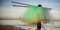 Мужчина несет рыболовную сеть. Архивное фото