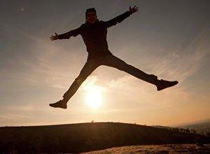 Прыжок парня на фоне рассвета. Архивное фото