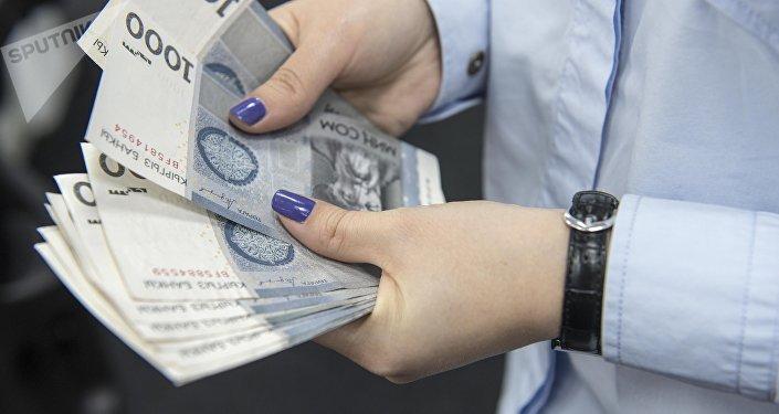 Женщина пересчитывает 1000 сомовые купюры. Архивное фото