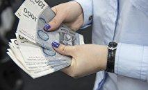 Женщина пересчитывает деньги. Архивное фото