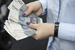 Женщина пересчитывает 1000-сомовые купюры