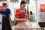 Девушки в национальных костюмах голосуют на выборах президента Российской Федерации на избирательном участке №4660 в Сочи.