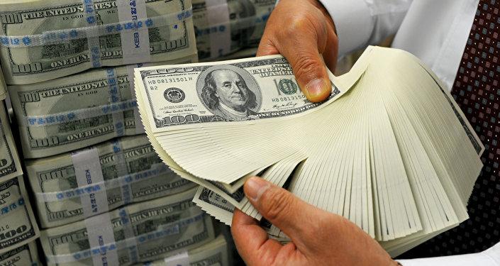Сотрудник банка держит банкноты доллара США. Архивное фото