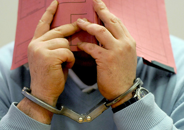 Мужчина в наручнике закрывает лицо. Архивное фото