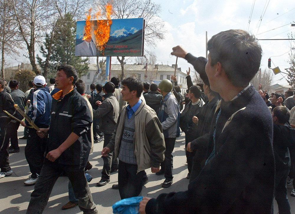 Митингге чыккан жүздөгөн адам Аскар Акаевдин күйүп жаткан сүрөтүнүн алдынан өтүп келе жатат. 2005-жыл, 21-март, Ош