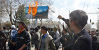 Протестующие оппозиционеры проходят мимо горящего плаката президента Кыргызстана Аскара Акаева в городе Ош