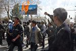 Протестующие оппозиционеры проходят мимо горящего плаката президента Кыргызстана Аскара Акаева