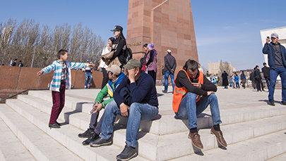 Люди сидят у памятника Манас на площади Ала-Тоо в Бишкеке. Архивное фото