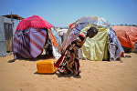 Сомалийская девочка тащит канистру с водой из колодца на окраине столицы