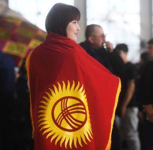 Кыргызстандын желегин жамынып турган кыз. Архив