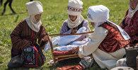 Женщины в национальных костюмах укладывают ребенка в колыбель на фестивале кочевников в ущелье Чункурчак. Архивное фото