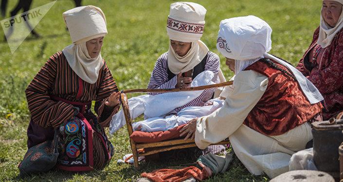 Женщины в национальных костюмах укладывают ребенка в колыбель. Архивное фото
