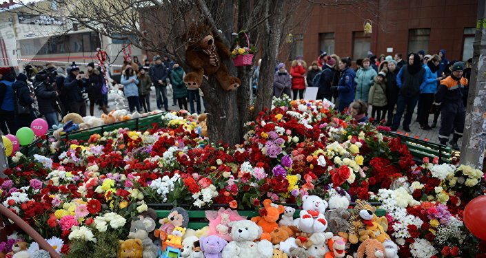 Цветы и мягкие игрушки возле здания торгового центра «Зимняя вишня» в Кемерово, где произошел пожар.