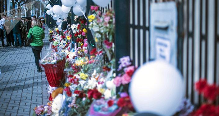 Женщина у ворот посольства России в Бишкеке, где люди оставляют цветы и игрушки в память о погибших при пожаре в ТЦ в Кемерово