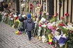 Ребенок у ворот посольства России в Бишкеке, где люди оставляют цветы и игрушки в память о погибших при пожаре в ТЦ в Кемерово. Архивное фото