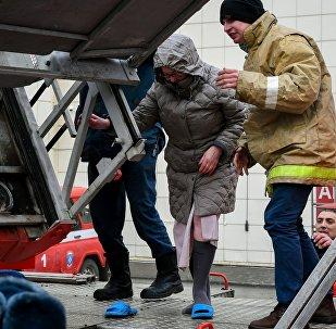 Сотрудники пожарной охраны МЧС помогают посетителям выбраться из торгового центра «Зимняя вишня» в Кемерово, где произошел пожар.