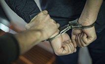 Арестованный мужчина в наручниках