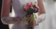 Девушка с цветами в руке. Архивное фото