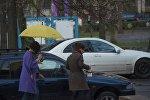 Девушки с зонтом идут по улице во время дождя в Бишкеке. Архивное фото