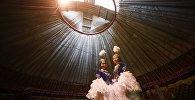Девушки в традиционных костюмах в юрте во время празднования Нооруза. Архивное фото