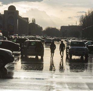 Горожане идут по площади Ала-Тоо в Бишкеке после дождя. Архивное фото