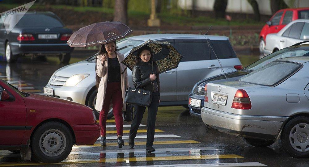 Девушки с зонтами переходят дорогу во время дождя. Архивное фото