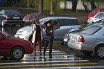 Девушки с зонтами переходят дорогу во время дождя в центре Бишкека. Архивное фото