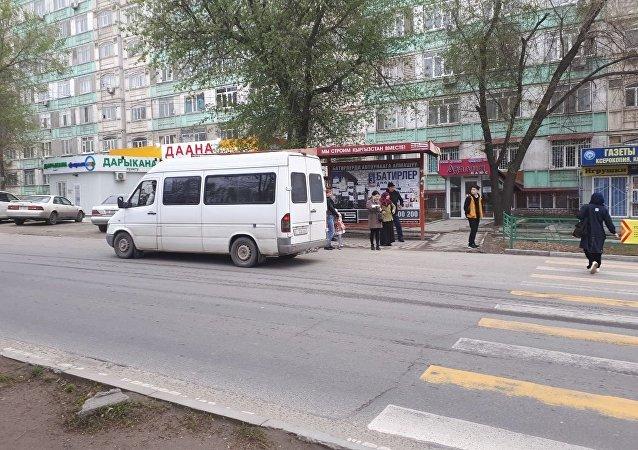 Люди садятся в маршрутку на остановке по улице Киевской в Бишкеке