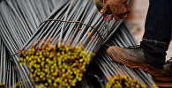 Работник использует плоскогубцы чтобы разрезать металлическую проволоку. Архивное фото