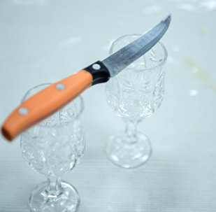 Нож поставленный на рюмку на столе. Архивное фото