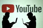 Силуэты людей с ноутбуками на фоне логотипа YouTube. Архивное фото