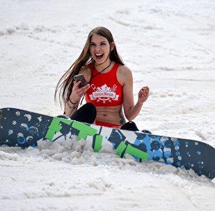 Девушка со смартфоном катается на сноуборде. Архивное фото