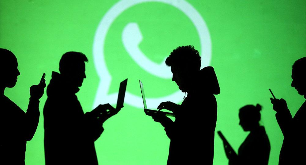 Силуэты людей на фоне логотипа мессенджера WhatsApp. Архивное фото
