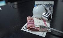 Деньги и лампочка на столе. Архивное фото