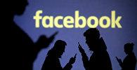 Силуэты мобильных пользователей видны рядом с экранной проекцией логотипа Facebook. Архивное фото