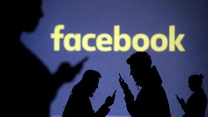 Силуэты людей с телефонами на фоне логотипа Facebook. Иллюстративное фото