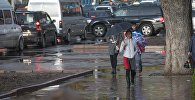 Девушка с зонтом во время дождя в Бишкеке. Архивное фото