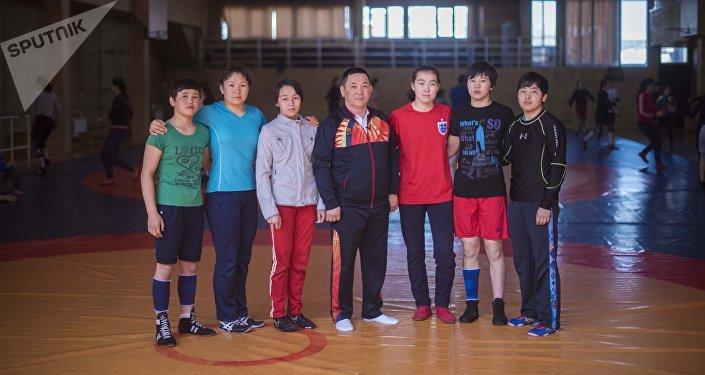 Тренер по женской борьбе среди кадетов Усоналы Рыскулов с воспитанниками в спортивном зале