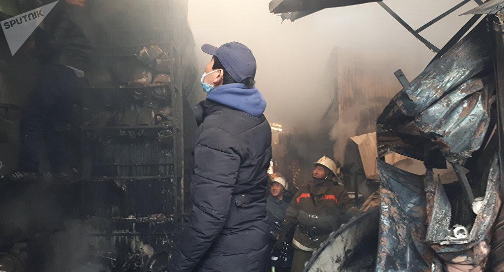 Торговцы выводят свои товары после крупного пожара на территории Ошского рынка в Бишкеке