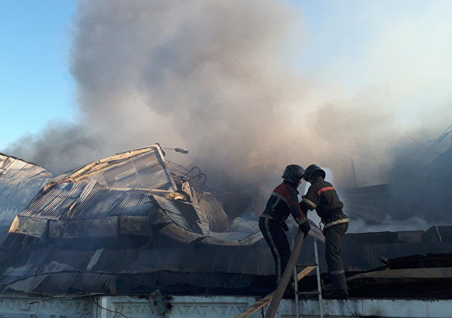 Сотрудники МЧС во время тушения крупного пожара на территории Ошского рынка в Бишкеке