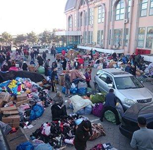 Продавцы на месте пожара на территории Ошского рынка в Бишкеке. Архивное фото