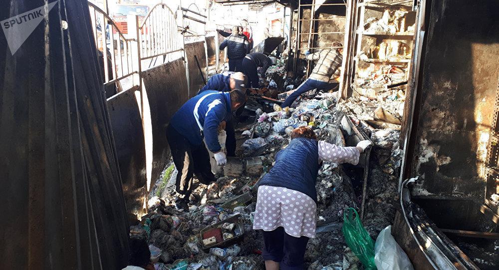 Продавцы вывозят свои товары во время пожара на территории Ошского рынка в Бишкеке