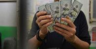 Молодой парень пересчитывает доллары США. Архивное фото