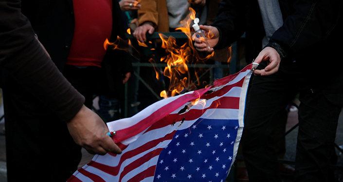 Протестующие против воздушных ударов по Сирии военными США, Великобритании и Франции сжигают флаг США